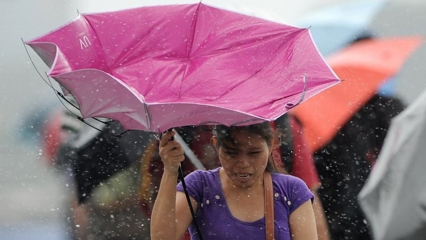 A woman struggles to control her broken umbrella as she walks on an overpass in the rain in Manila on September 22, 2013.