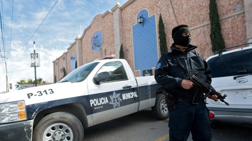A member of the local police stands guard on January 31, 2012 in Ciudad Juarez. Gunmen armed with assault rifles opened fire on a group of people after an amateur baseball game in northern Mexico, killing 10 including a six-year-old girl, authorities said Monday.