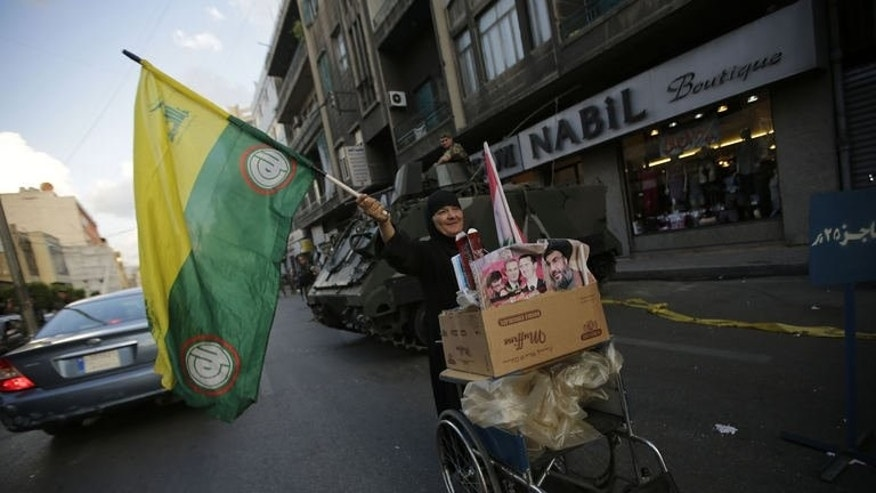 A Lebanese Shiite woman waves a Hezbollah flag as she pushes a cart past a checkpoint in the southern suburb of Beirut on September 23, 2013.
