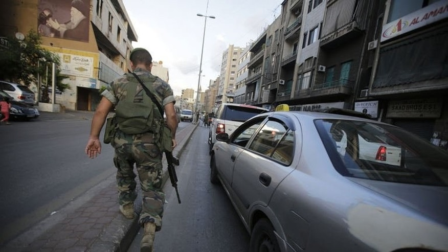 A Lebanese soldier walks towards a checkpoint in the southern suburb of the capital Beirut on September 23, 2013.
