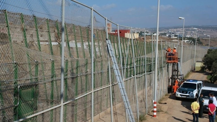 A handout picture on September 17, 2013 shows employees repairing a border fence after migrants tore it down to break from Morocco into Spain.