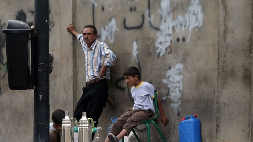 Young Syrian refugees and their father prepare coffee to sell in a street in Beirut on September 18, 2013.