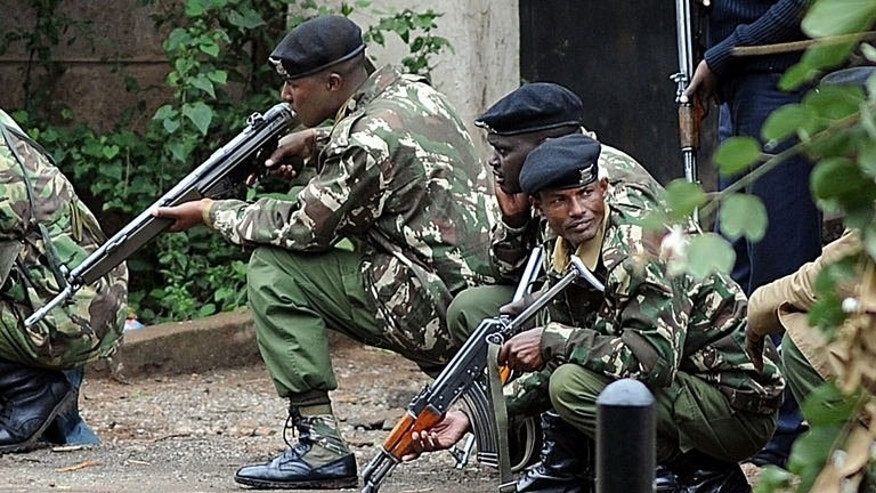 "Armed Kenyan police take cover outside the Westgate mall in Nairobi on September 23, 2013. Kenyan troops say they are ""in control"" of the mall, with all the hostages trapped by Islamist gunmen believed to have been freed."