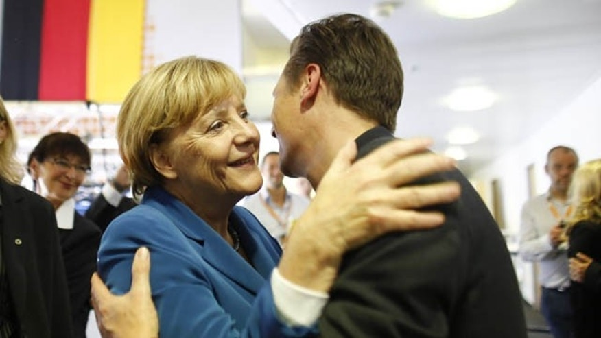 September 22, 2013: German Chancellor Angela Merkel, chairwoman of the Christian Democratic party, CDU, greets a supporter at the party headquarters after the national elections in Berlin Sunday.