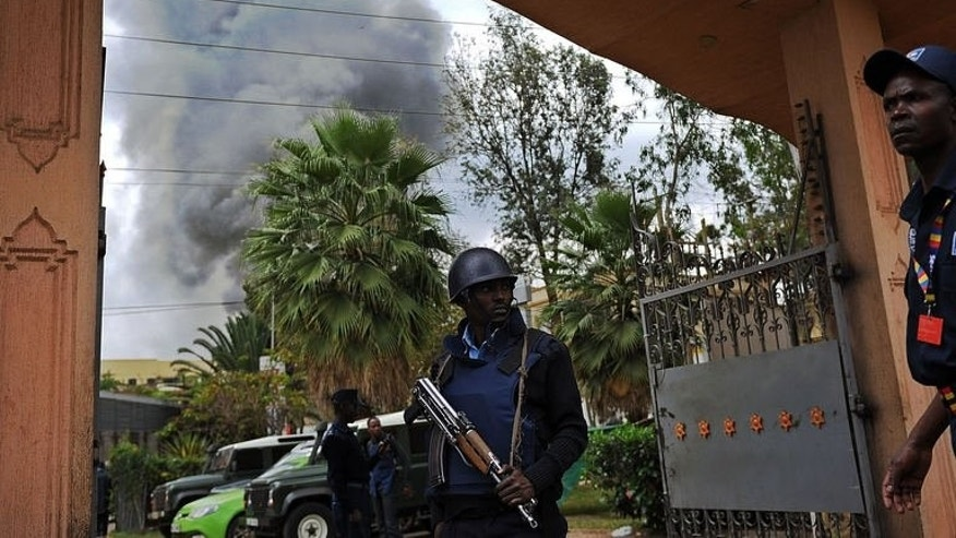 A Kenyan police officer mans the entrance of a building in the vicinity of the beseiged Westgate shopping mall in Nairobi on September 23, 2013, from where a column of smoke rises following a loud explosion.