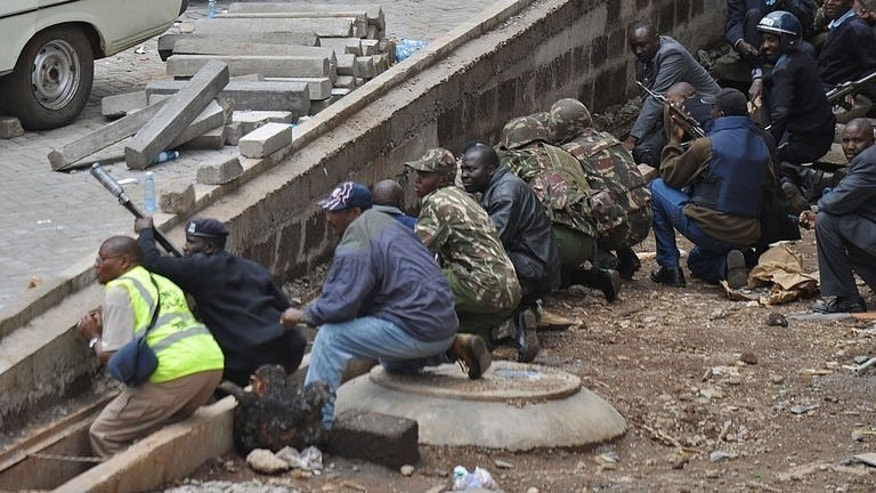Kenyan security personnel, crouched behind a ledge, watch on September 23, 2013 as a column of smoke rises from the beseiged Westgate shopping mall in Nairobi.
