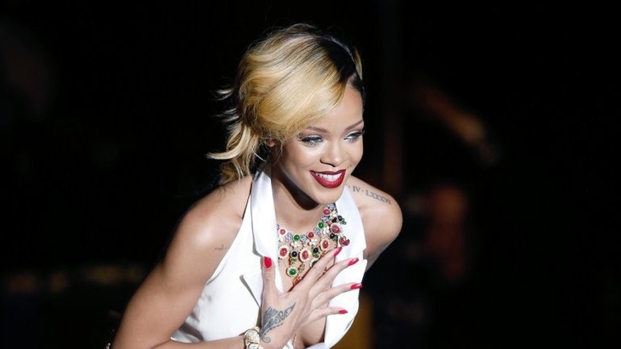 Barbadian singer Rihanna performs on stage in Monaco, on July 10, 2013. Thai authorities say two men have been arrested on suspicion of possessing a protected primate after Rihanna posted a picture of herself online holding the creature.
