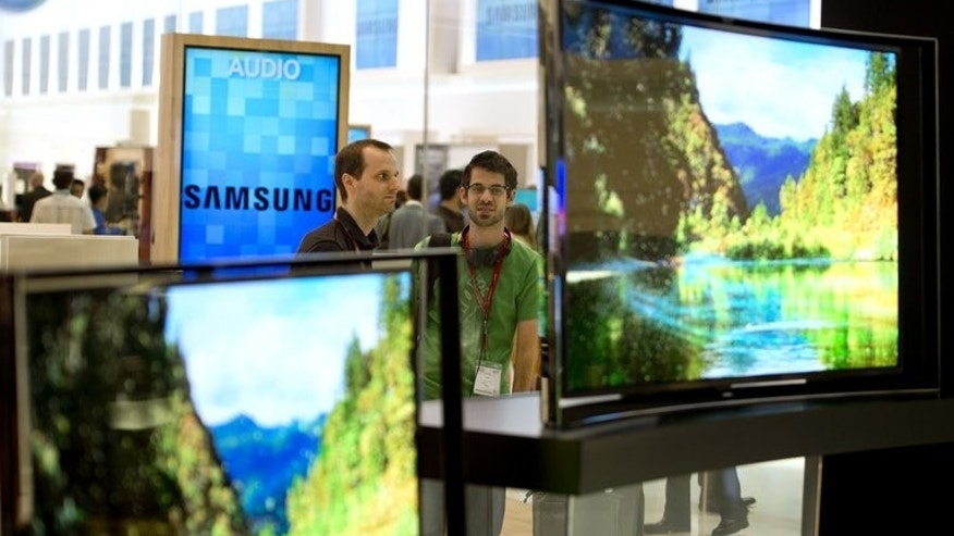 People look at curved OLED TV screens in Berlin on September 5, 2013.