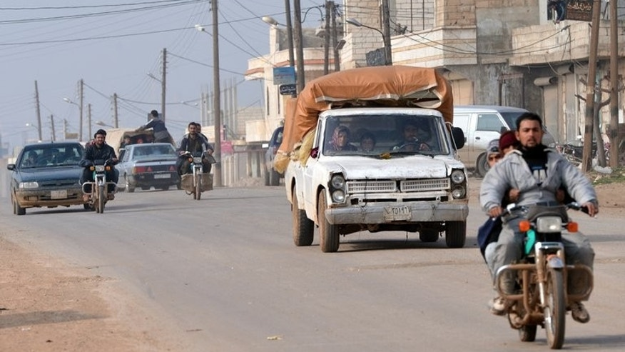 Residents drive motorcycles and cars to flee during fighting between rebels and regime forces close to Hama, on January 27, 2013.