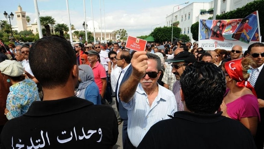 A protester shows his press card in front of policemen during a demonstratio on September 16, 2013 at the Kasbah Square in Tunis.