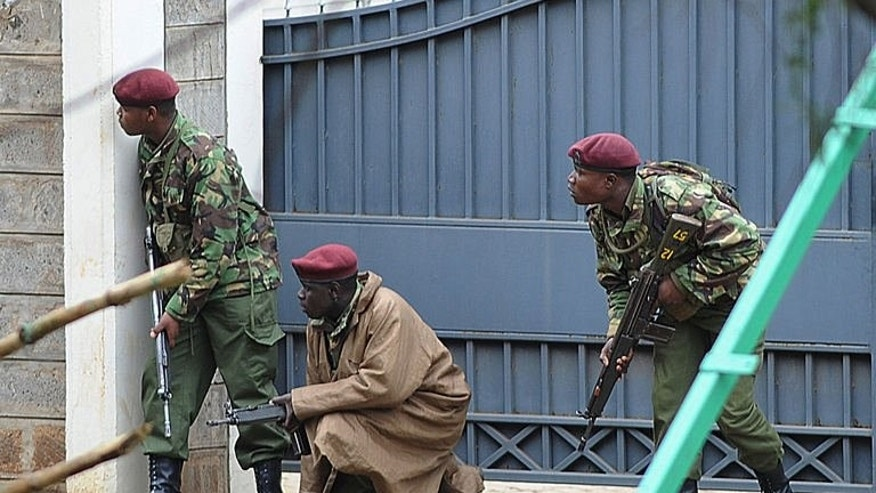 Armed Kenyan policemen take cover outside the Westgate mall in Nairobi on September 23, 2013.