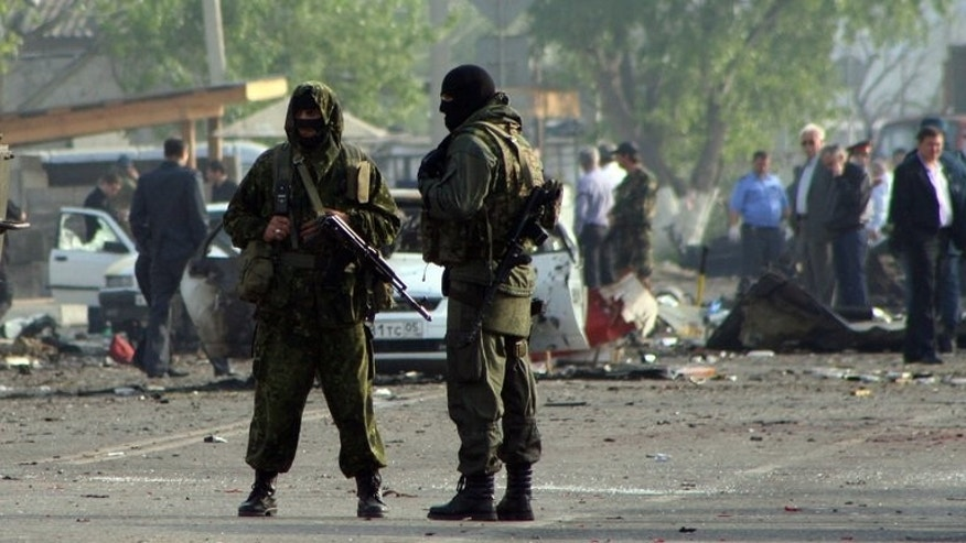 File picture shows special forces officers guarding the site of two blasts in the Dagestan's capital Makhachkala early on May 4, 2012.