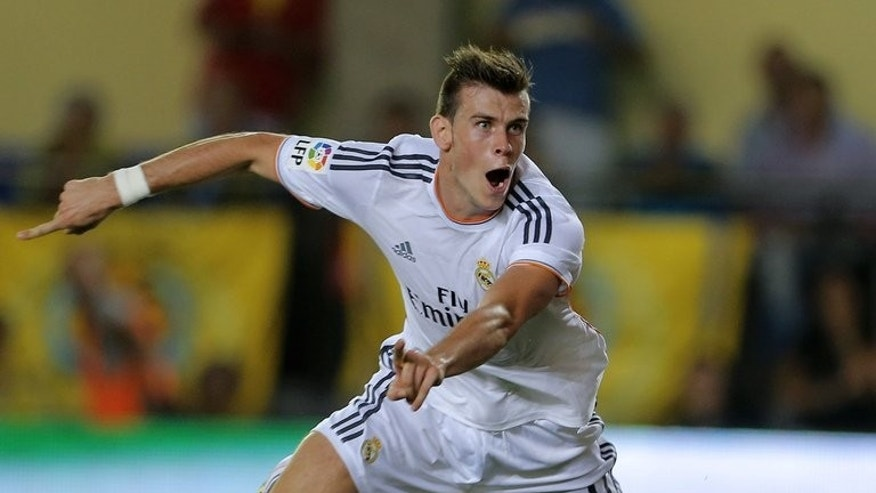 Real Madrid's Welsh striker Gareth Bale celebrates after scoring in the Spanish league match against Villarreal CF in Villareal on September 14, 2013. Real Madrid coach Carlo Ancelotti has confirmed that Bale will be fit to finally make his home debut for the club in the Madrid derby against Atletico on Saturday.