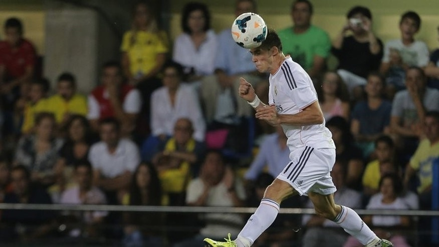 Real Madrid's Welsh striker Gareth Bale heads the ball during the Spanish league football match against Villarreal CF in Villareal on September 14, 2013. Real Madrid coach Carlo Ancelotti has confirmed that Bale will be fit to finally make his home debut for the club in the Madrid derby against Atletico on Saturday.