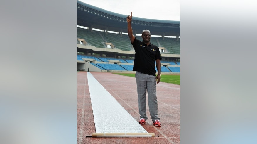 Disgraced drugs cheat Ben Johnson stands next to a 100 metre-long anti-doping petition at the Olympic Stadium in Seoul on September 24, 2013. Johnson has returned to Seoul's Olympic Stadium, 25 years to the day of the steroid-assisted 100m final victory that destroyed his career and reputation.