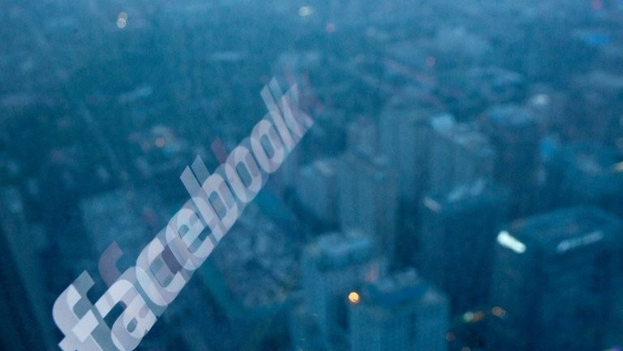 A computer screen displaying the Facebook logo reflected in a window before the Beijing skyline on May 16, 2012.