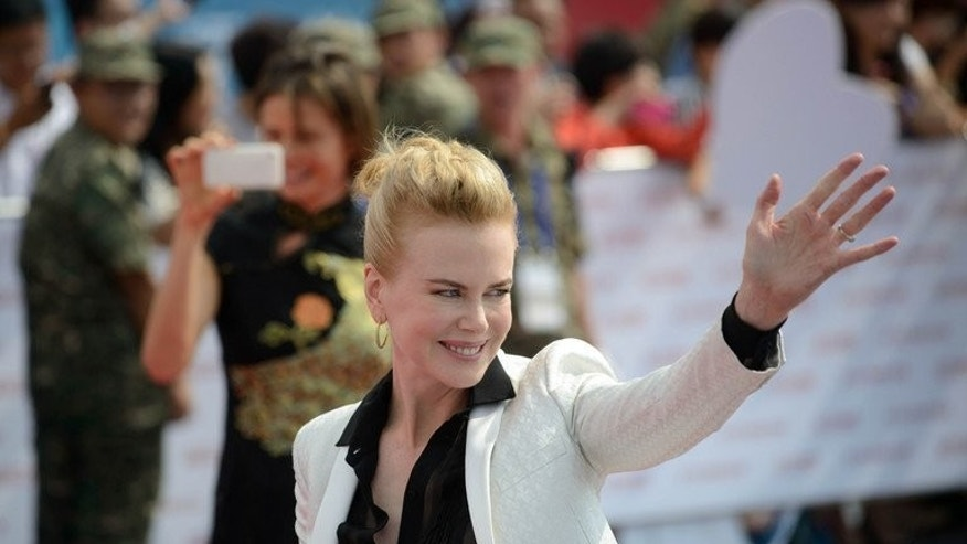Actress Nicole Kidman waves during a red carpet event showcasing plans for the ambitious Oriental Movie Metropolis in Qingdao on September 22, 2013.