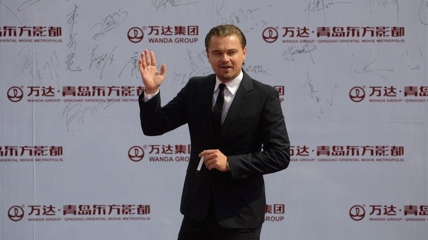 Actor Leonardo DiCaprio waves during a red carpet event showcasing plans for the ambitious Oriental Movie Metropolis in Qingdao on September 22, 2013.