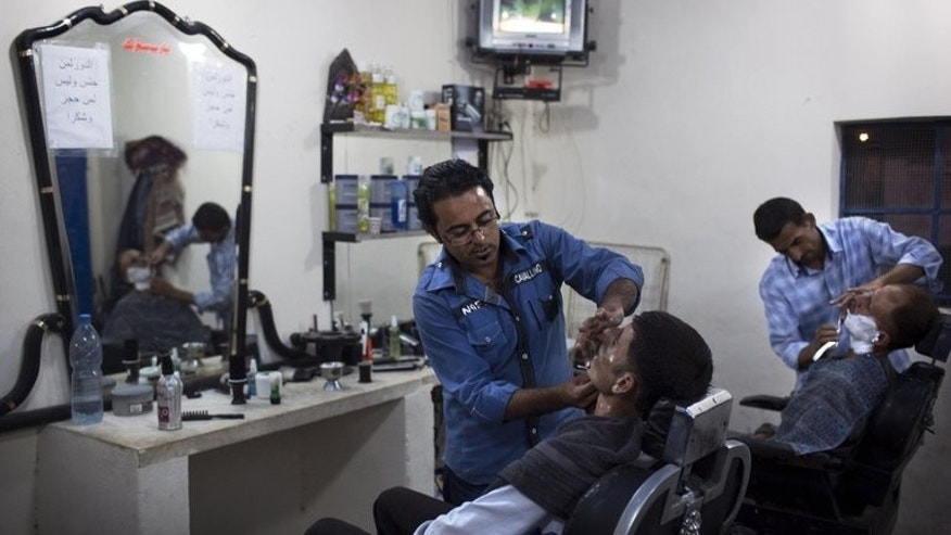 A Syrian barber gives a shave to a client at his shop in the Sheikh Najjar industrial zone near Aleppo, on September 20, 2013. War had reduced Syria's largest industrial complex to a ghost town, but displaced residents of nearby Aleppo are now creating a bustling lifestyle amid the abandoned factories and warehouses.