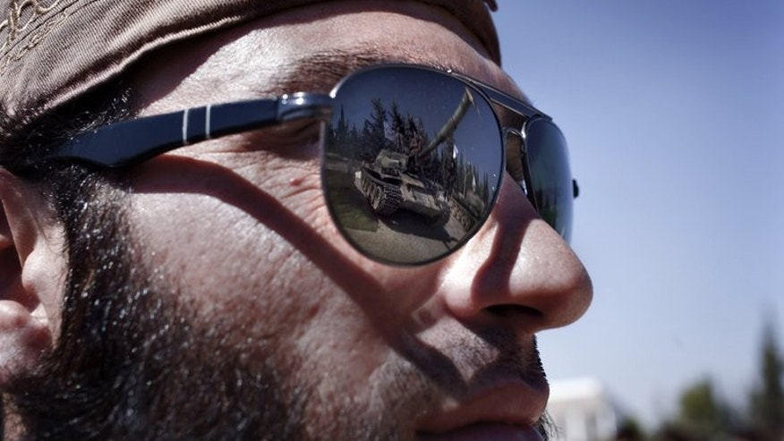 A tank is reflected on the sunglasses of a Syrian rebel on the outskirts of Aleppo, on September 13, 2013. War had reduced Syria's largest industrial complex to a ghost town, but displaced residents of nearby Aleppo are now creating a bustling lifestyle amid the abandoned factories and warehouses.
