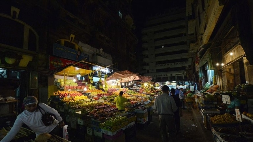 Egyptians walk at a fruit market in downtown Cairo on October 18, 2012. Egypt will impose a sharp cut in the price of fruits and vegetables if they do not come down on their own by next week, the supply and domestic trade minister said Tuesday.