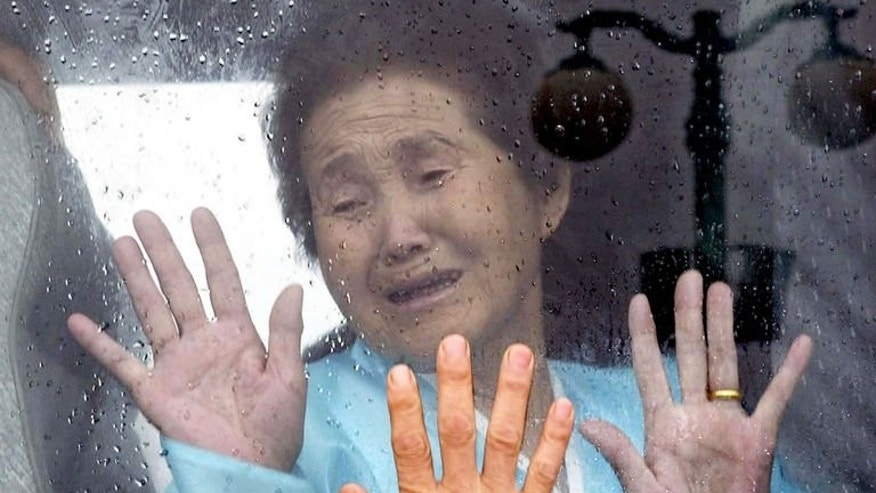 A North Korean bids farewell to her South Korean relative from a bus after a reunion in North Korea on 13 July 2004.