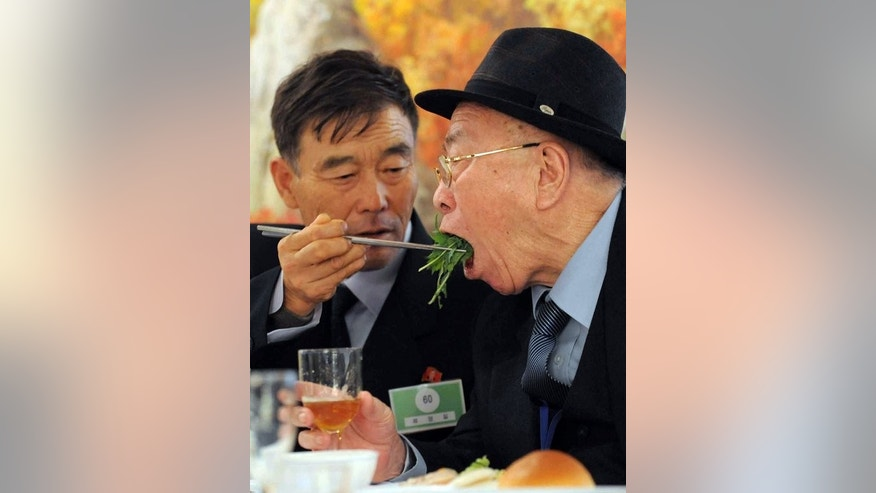 North Korean Ryu feeds his South Korean father during a luncheon for separated families on November 4, 2010.