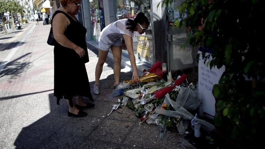 Women lay flowers on September 19, 2103 at the spot where anti-fascist musician Pavlos Fyssas, was murdered in Piraeus, Greece. The killing has prompted authorities to take a harder stance against Golden Dawn.