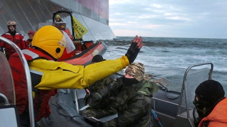 A camouflage-clad masked Russian Coast Guard officer points a knife at a Greenpeace International activist (L) in the Pechora Sea, September 18, 2013.