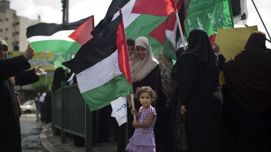 A Palestinian girl holds the national flag during a protest organised by the ruling Islamic Hamas movement in Gaza city on September 24, 2013.