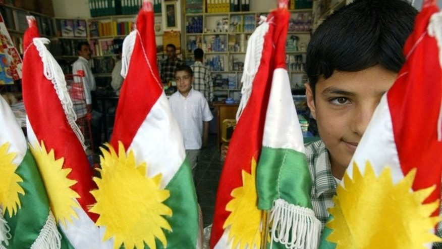 An Iraqi boy looks at Kurdish flags on display in Arbil, on June 12, 2004. Voters in Iraq's Kurdish region may have had differing views at the ballot box during weekend polls, but there is one dream which unites virtually all of them: an independent state.