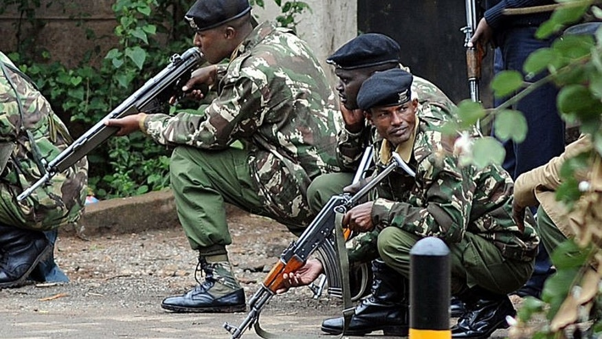 """Armed Kenyan police take cover outside the Westgate mall in Nairobi on September 23, 2013. Kenyan troops say they are """"in control"""" of the mall, with all the hostages trapped by Islamist gunmen believed to have been freed."""
