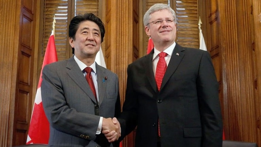 Canada's Prime Minister Stephen Harper (R) shakes hands with his Japanese counterpart Shinzo Abe during a meeting in Harper's office on Parliament Hill in Ottawa, Canada on September 24, 2013.