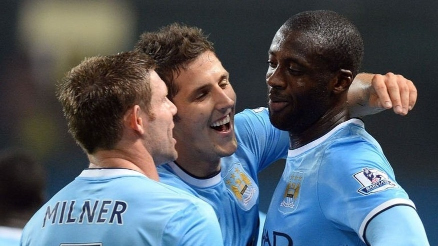 Manchester City's Ivorian defender Yaya Toure (R) celebrates with Montenegrin forward Stevan Jovetic (C) and English midfielder James Milner (L) after scoring the third goal during the League Cup football match between Manchester City and Wigan Athletic at The Etihad Stadium in Manchester, north west England, on September 24, 2013. City won 5-0.