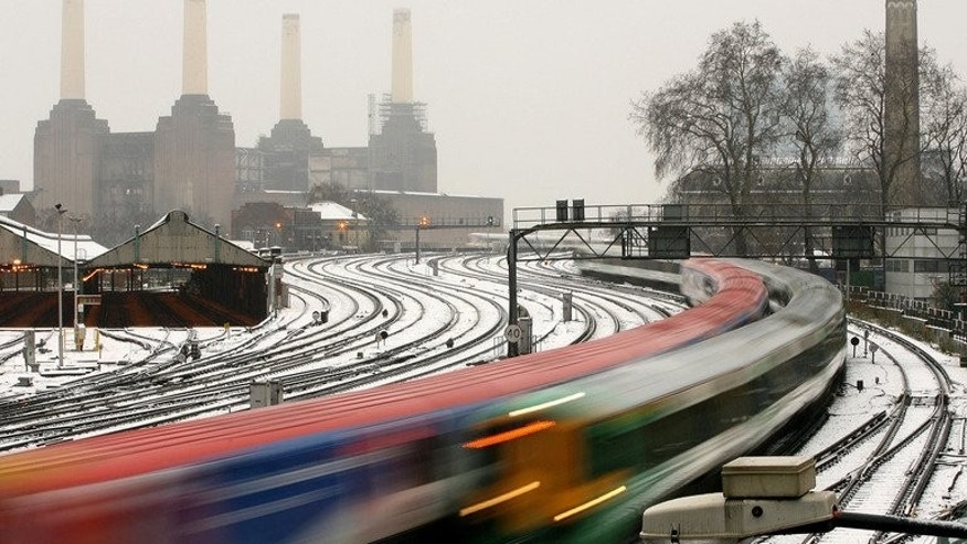 Commuter trains run past Battersea Power Station as snow falls in central London, February 8, 2007. British rail operator National Express announced Tuesday it has won a 1.6-billion-euro ($2.2-billion) contract to operate two regional services in Germany's most populous state, North Rhine-Westphalia.