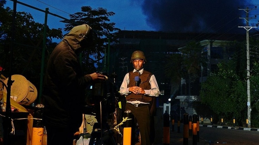 A Kenyan TV presenter stands in front of smoke rising from Westgate Mall on September 23, 2013.There were no leaks or 'chatter' intercepted from Somalia's Shebab Islamist rebels ahead of the attack on Nairobi's Westgate shopping mall, intelligence sources from two foreign countries told AFP Tuesday.