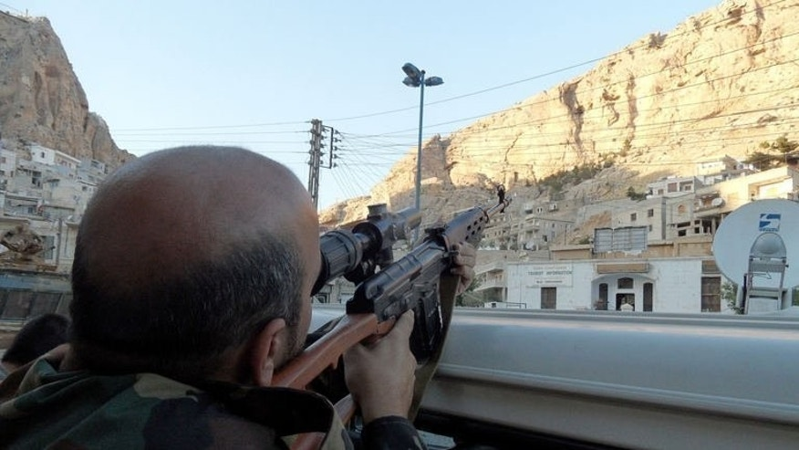 A Syrian pro-regime soldier aims his rifle as he patrols the Christian town of Maalula, on September 11, 2013. Nearly 40 nuns and orphans are trapped inside a convent in the Syrian Christian town of Maalula, where regime troops are battling rebel forces, according to the Greek Orthodox Patriarchate.
