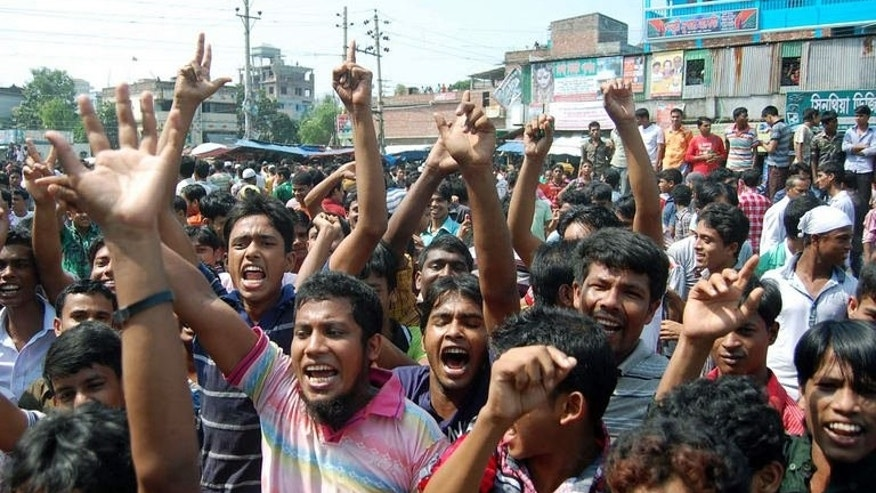 Bangladeshi garment workers shout slogans during a protest in Narayanganj on September 24, 2013.