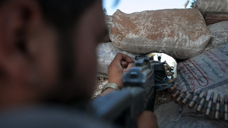 A Syrian rebel points his rifle from his bunker in Idlib, on June 14, 2013. Three months after a new emir stepped in, Qatar's political clout has shrunk following the ouster of Egypt's Islamist president and with Riyadh emerging as the Syrian opposition's main backer, analysts say.