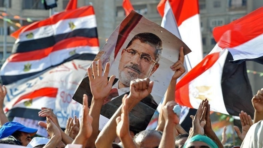 Muslim Brotherhood supporters hold a portrait of Mohamed Morsi during a rally outside the Rabaa al-Adawiya mosque in Cairo, on July 24, 2013. Three months after a new emir stepped in, Qatar's political clout has shrunk following the ouster of Egypt's Islamist president and with Riyadh emerging as the Syrian opposition's main backer, analysts say.
