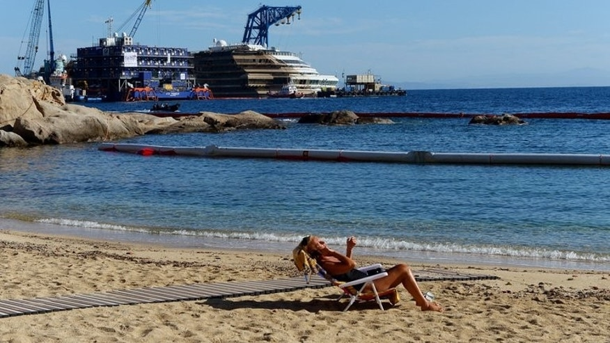 A woman sunbathes on September 18, 2013, in front of the wreck of Italy's Costa Concordia cruise ship, near the harbour of Giglio Porto.