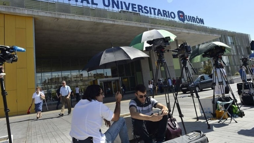 Media crews wait outside the Quiron University Hospital in Madrid on September 24, 2013 for the arrival of Spanish King Juan Carlos. The king is to have his left hip operated on for the eighth time since 2010 announced the royal palace. AFP PHOTO / GERARD JULIEN