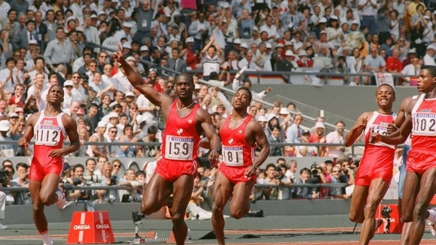 Ben Johnson (2nd L) celebrates after winning the 100m final at the Seoul Olympics on September 24, 1988 at Seoul's Olympic Stadium.