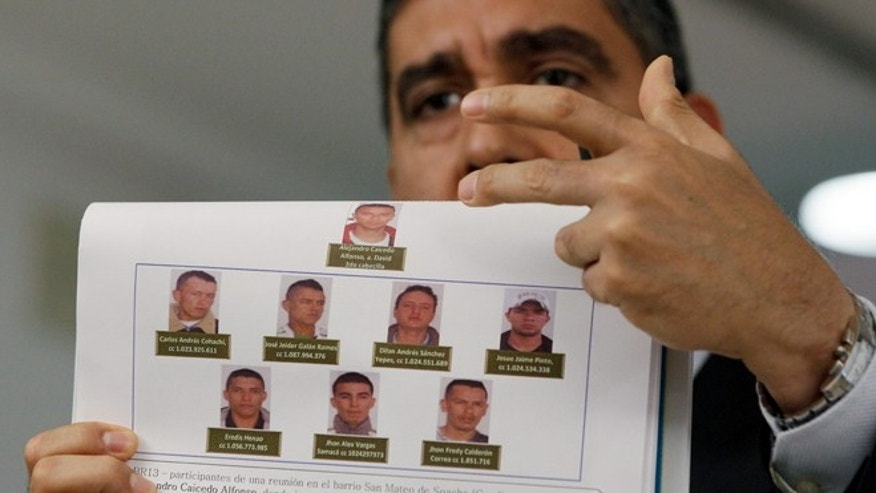 Venezuela's Interior and Justice Minister, Army Gen. Miguel Rodriguez Torres displays photos of men suspected by the government of planning to assassinate Venezuela's President Nicolas Maduro and National Assembly President Disodado Cabello, at a news conference at his office in Caracas, Venezuela, Monday Aug. 26, 2013.  Rodriguez Torres said that the group consists of 10 Colombian men, and that two have been arrested. (AP Photo/Fernando Llano)