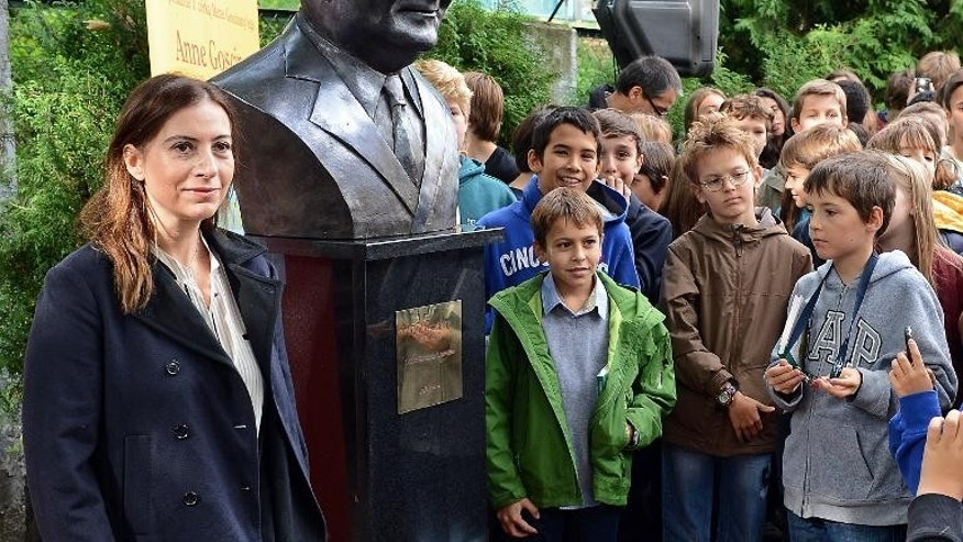 Anne Goscinny (L), daughter of the late French comic book writer Rene Goscinny, unveils a sculpture of her father at the French high school in Warsaw on September 25, 2013.