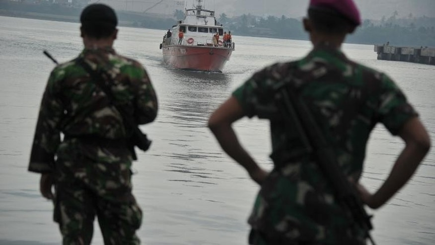 Indonesian marines look towards a rescue boat carrying asylum-seekers at Merak seaport in 2012.