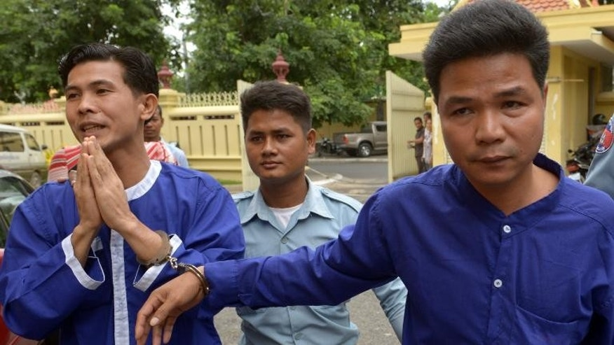 Born Samnang (left) and Sok Sam Oeun (right) are escorted by a prison guard to the Supreme Court in Phnom Penh, on September 25, 2013.