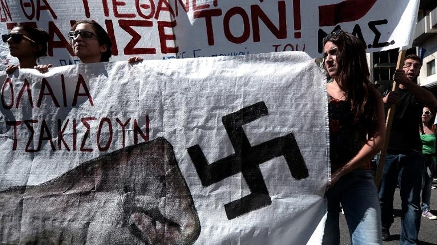 Greek students hold a banner showing a fist punching a Swastika while taking part in a march outside the Parliament in Athens during an anti-fascism protest on September 25, 2013.