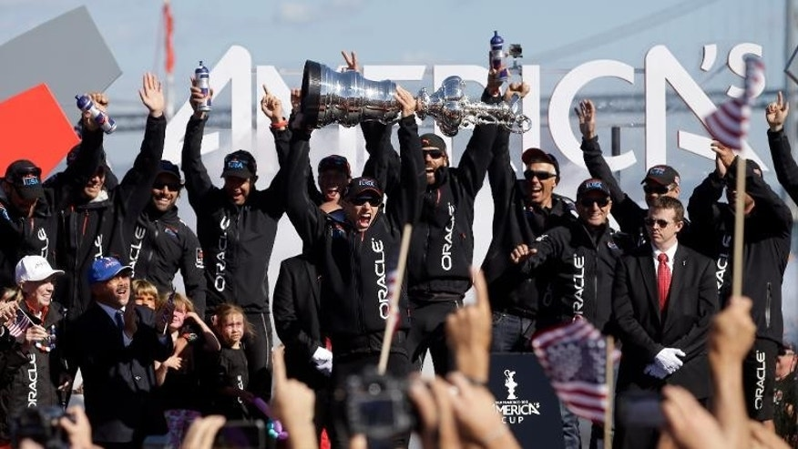 Oracle Team USA skipper James Spithill celebrates with the America's Cup trophy in San Francisco on September 25, 2013.