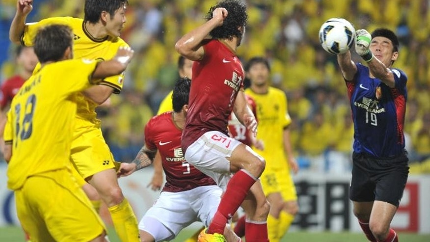 China's Guangzhou Evergrande goalkeeper Zeng Cheng (R) punches out the ball against Japan's Kashiwa Reysol in the AFC Champions League semi-final first leg at Hitachi Kashiwa Stadium in Kashiwa on September 25, 2013